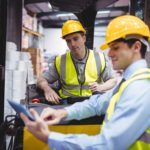 Warehouse worker talking with forklift driver