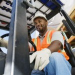 Low angle view of a happy mature male industrial worker driving forklift at workplace